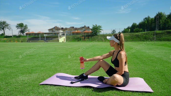 Woman having rest after training at stadium