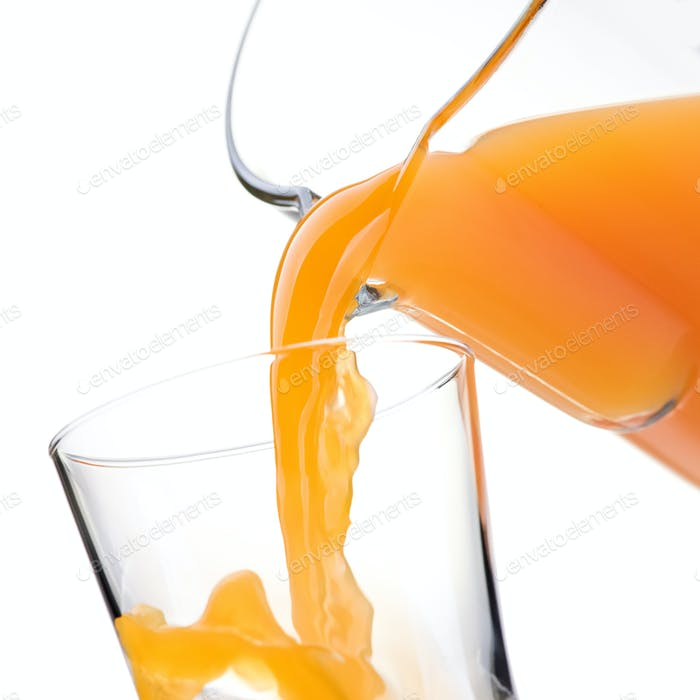 Pouring refreshing orange juice into a glass