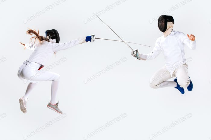The woman and man wearing fencing suit practicing with sword against gray