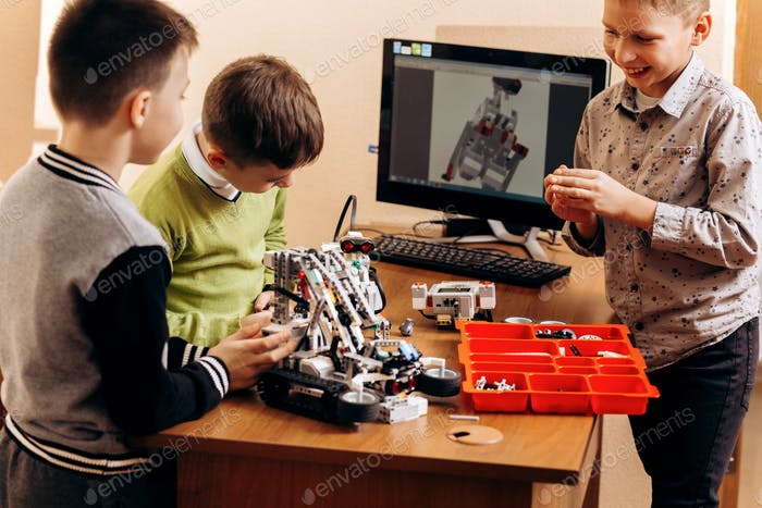 Three smart boys are making robots from the robotic constructor in the School of Robotics