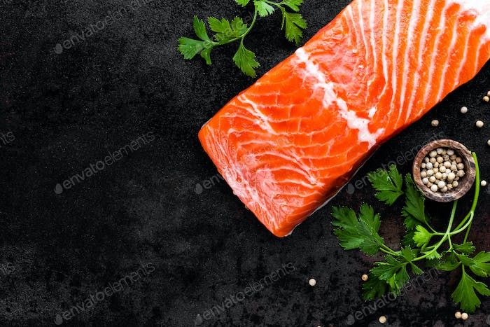 Fresh salmon fish fillet on black background, top view