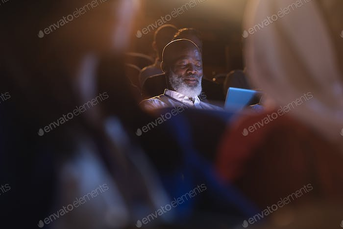 Old businessman looking at digital tablet while sitting in the auditorium