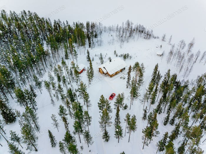 Aerial view of wooden log cabin or cottage in snow  winter forest by the lake in rural Finland