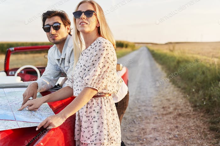 Couple with a map on the hood of the car