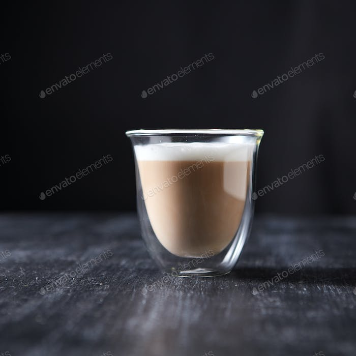 Freshly brewed cappuccino with foam in a glass cup on a black wooden table around a dark background