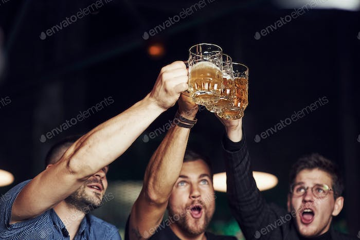 Knocking glasses. Three sports fans in a bar watching soccer. With beer in hands