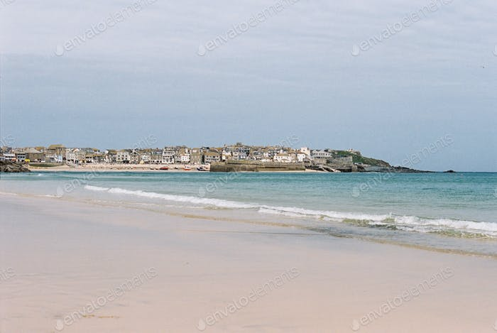 A small coastal village, small waves breaking on the shore of a curving beach