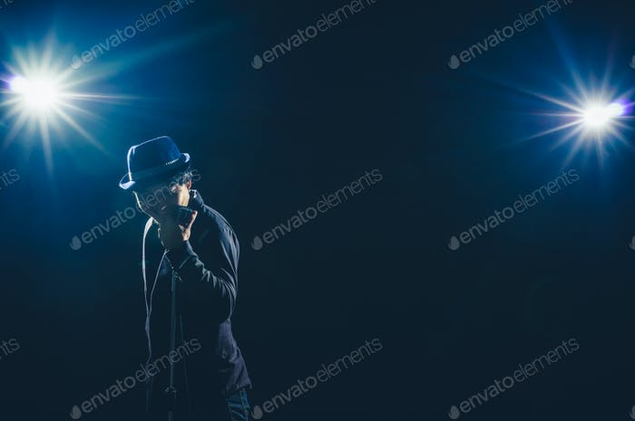 Asian Musician  singing a song with microphone on black background with spot light
