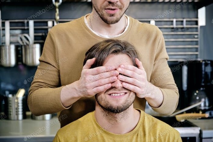 Young man keeping hands on eyes of his boyfriend