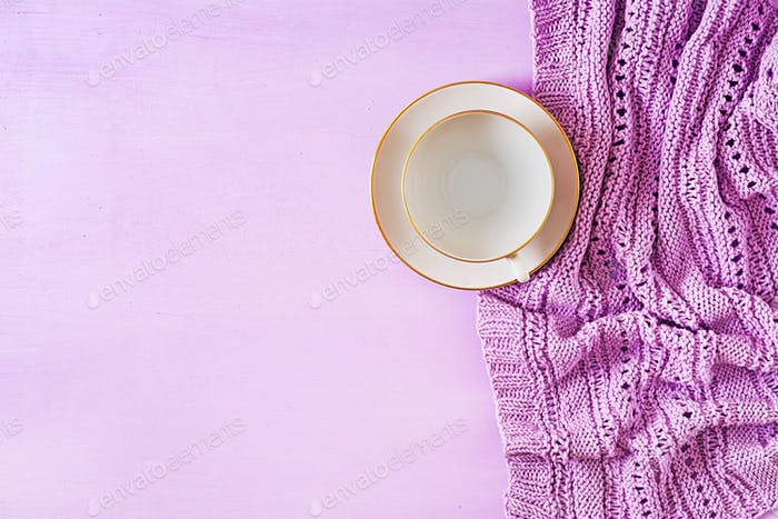 Empty white coffee cup  on violet background, close up photo knitted sweater with mug