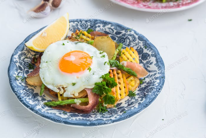 Fried egg with potato and jamon ham, spain cuisine, close view