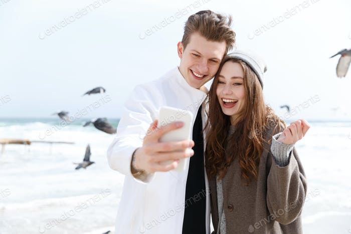 Cheerful young couple taking selfie with smartphone in autumn