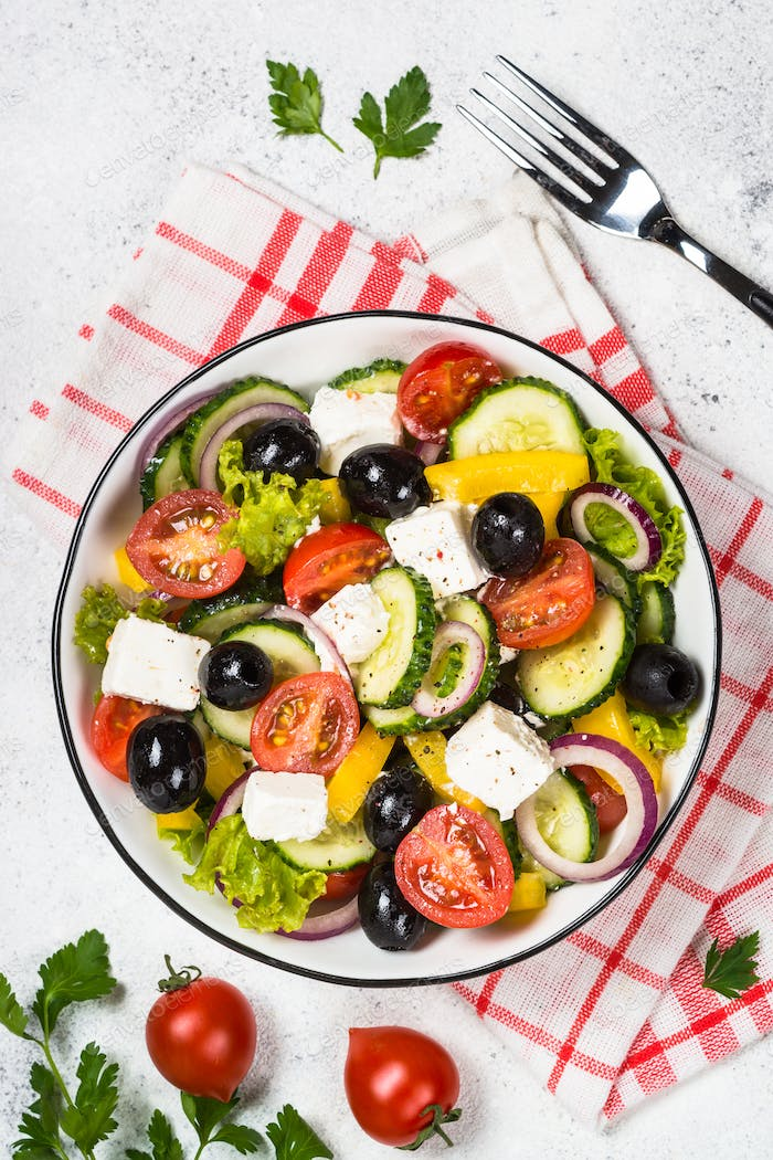 Greek salad in black plate on the table