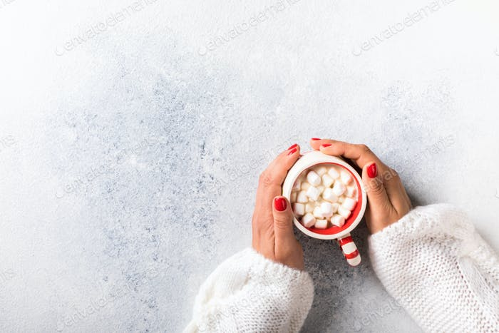 Female hands hold a cup of coffee with marshmallows . Holiday concept.