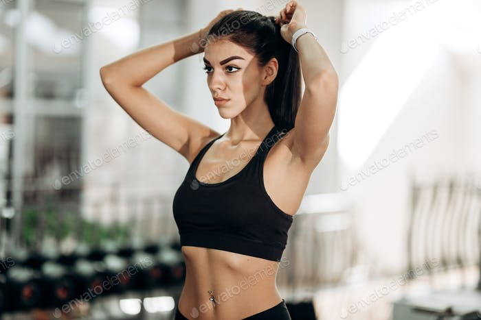 Pretty slim girl dressed in black sportswear is in the gym tying her hair