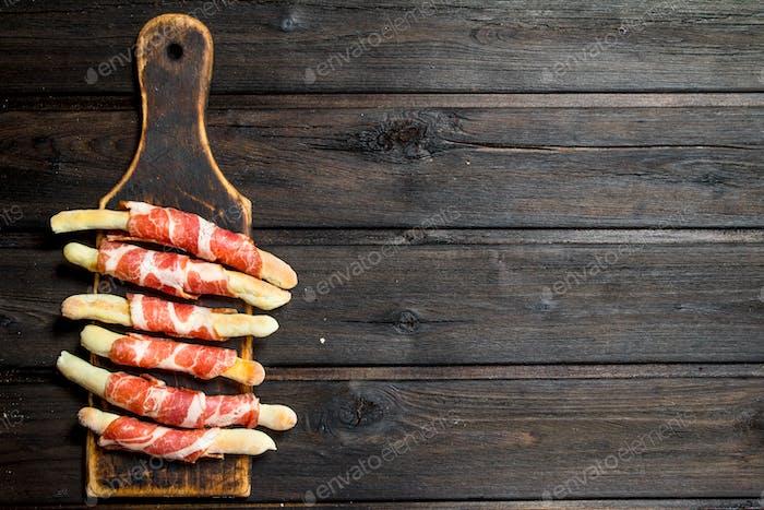 Meat appetizer on bread sticks.