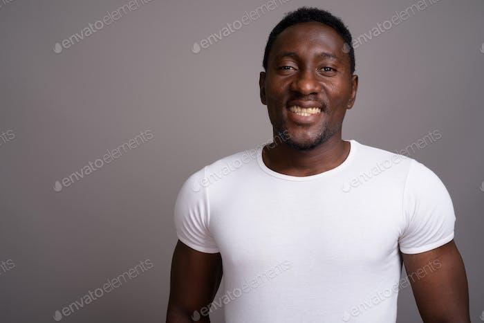 Junge gutaussehenden afrikanischen Mann vor grauen Hintergrund