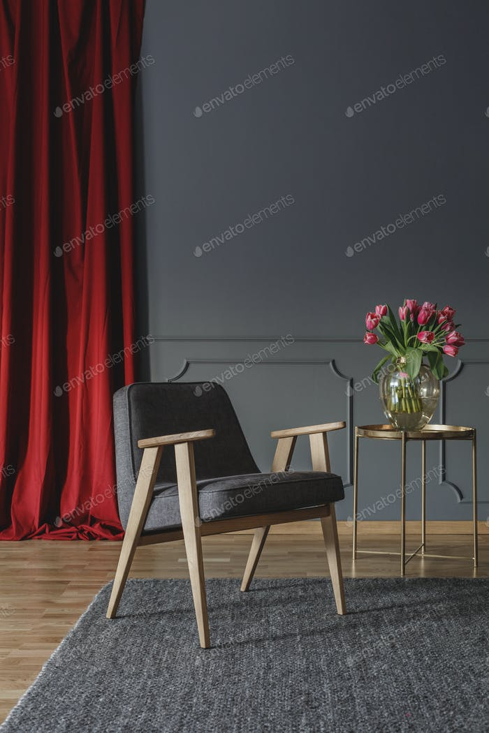 Grey wooden armchair on carpet next to gold table in living room