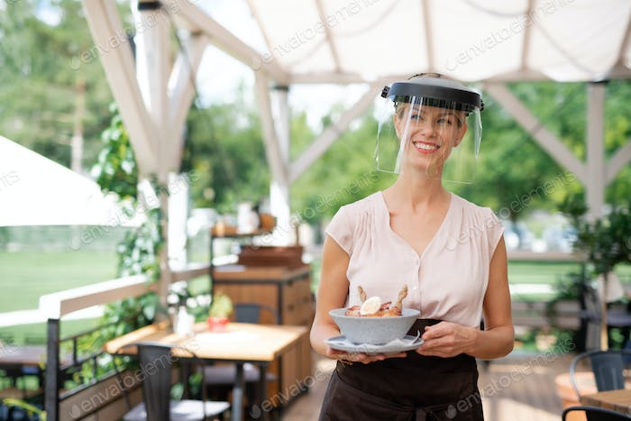 Waitress with protective face shield serving customers outdoors on terrace restaurant