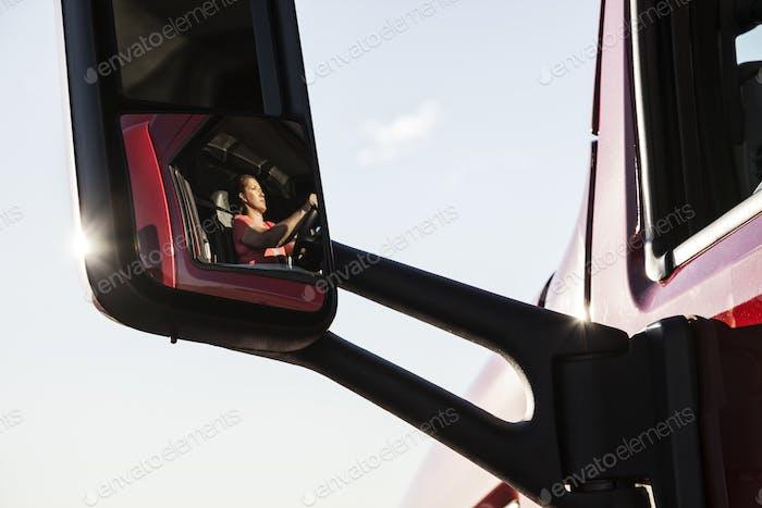 Ansicht einer kaukasischen Fahrerin in der Kabine ihres Nutzfahrzeugs.