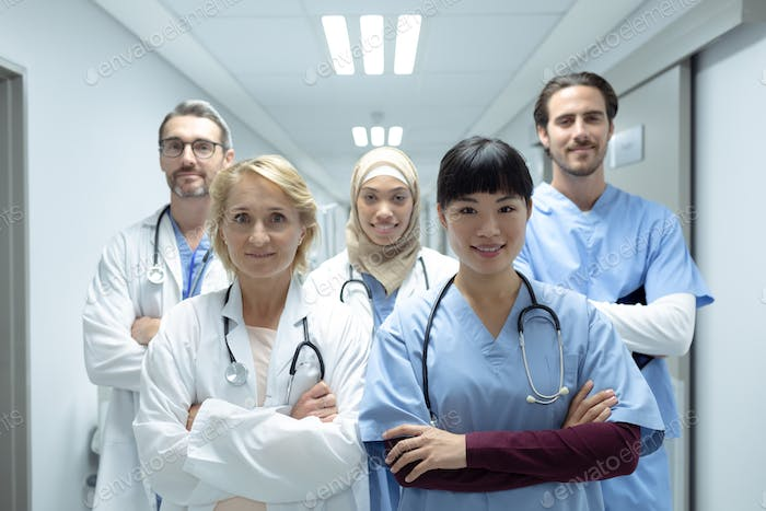 Portrait of diverse medical teams standing with arms crossed in the corridor at hospital