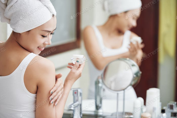 Smiling woman smoothing skin with lotion