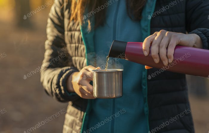 Close up of female hands pouring tea into mug