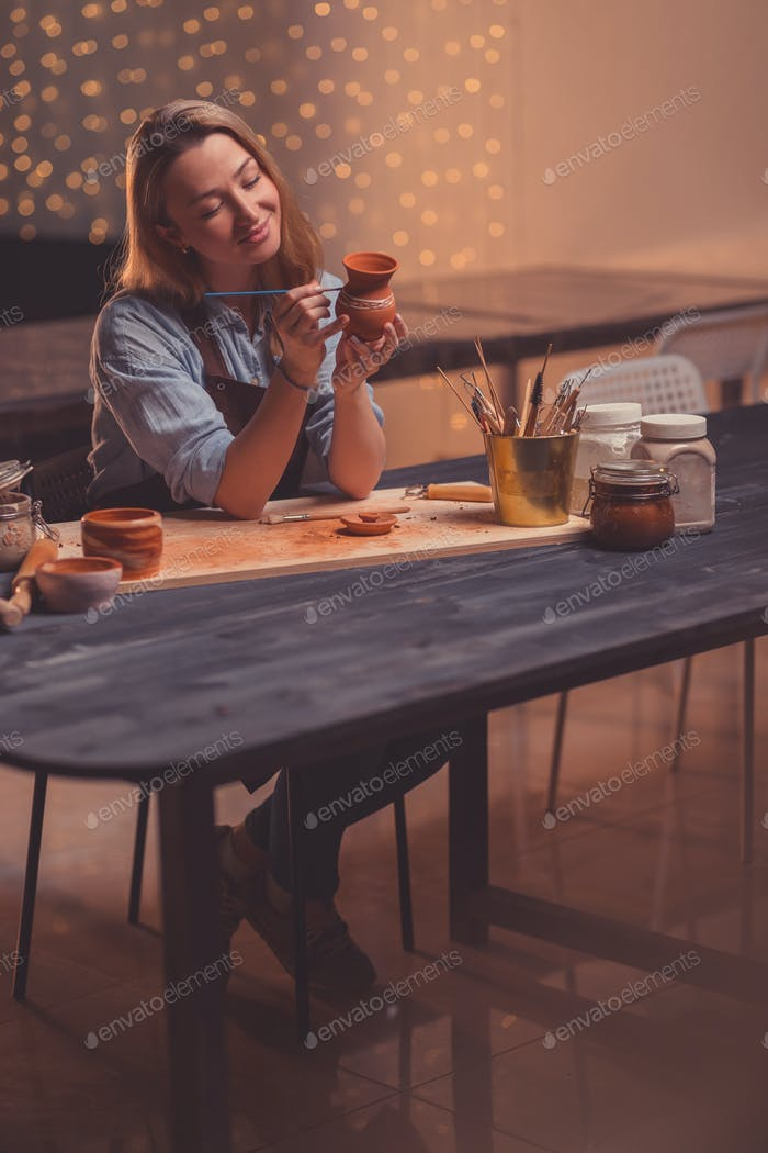 Smiling woman in a pottery studio