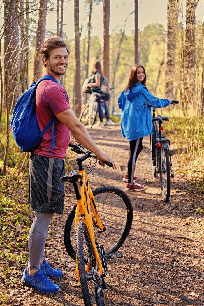 Smiling sporty man holds mountain bicycle.
