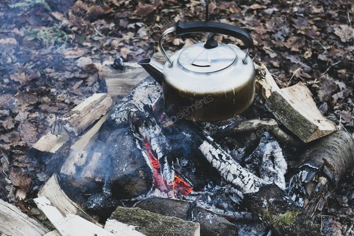High angle close up of metal kettle hanging over a campfire.