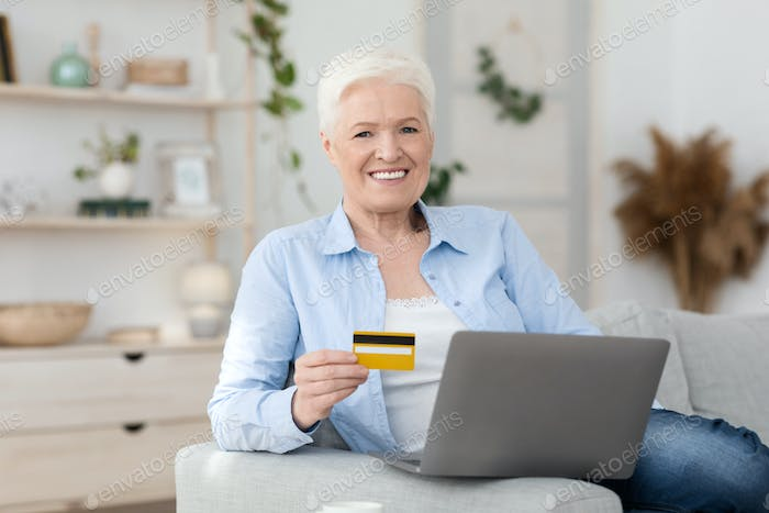 Online Shopping. Smiling Elderly Woman Posing With Laptop And Credit Card At Home