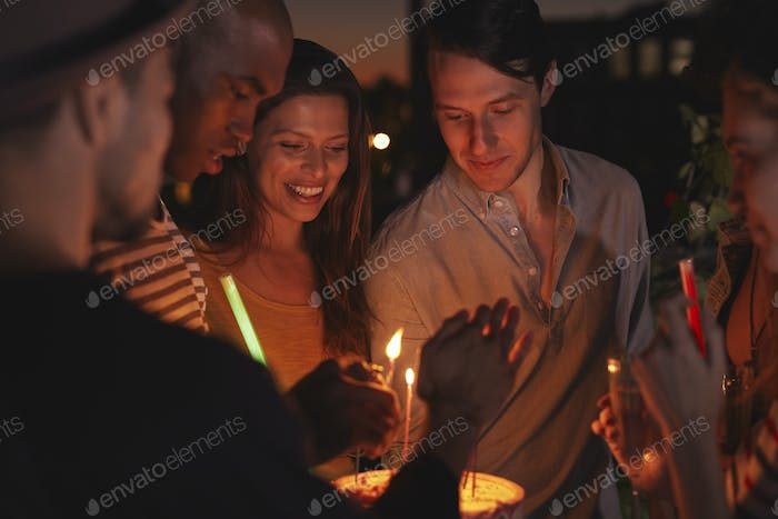 Friends on a rooftop lighting candles on a birthday cake