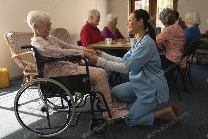 Side view of happy female doctor holding hands and talking with disable senior woman at home
