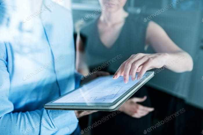Midsection of young businesspeople with tablet in an office, working.