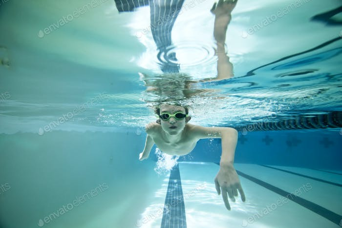 boy swimming laps under water