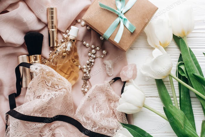 woman lace lingerie jewelry and perfume on soft fabric and tulips with empty greeting card