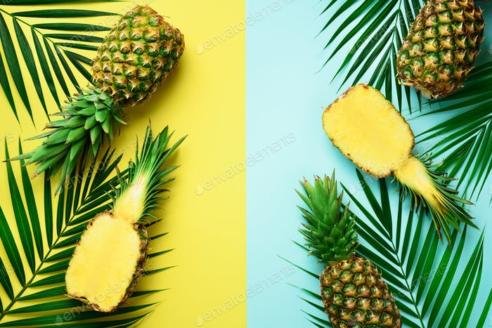 Pineapples, palm leaves on pastel colorful yellow and turquoise background with copy space. Creative