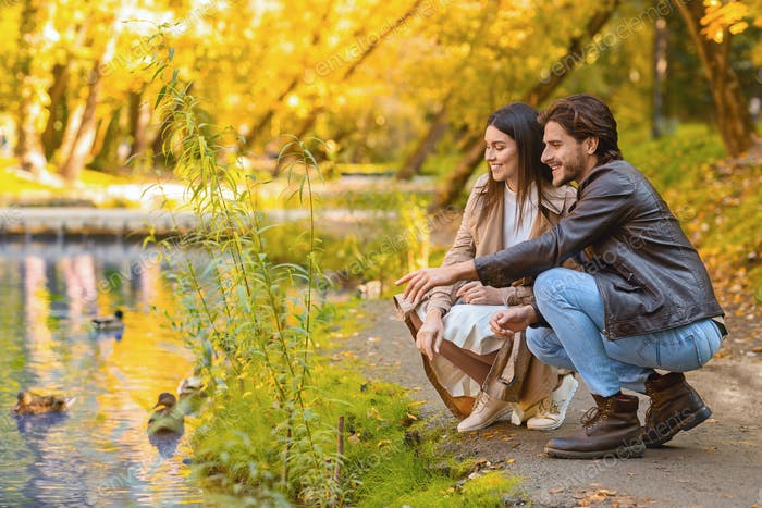 Romantic young couple looking at ducks at park