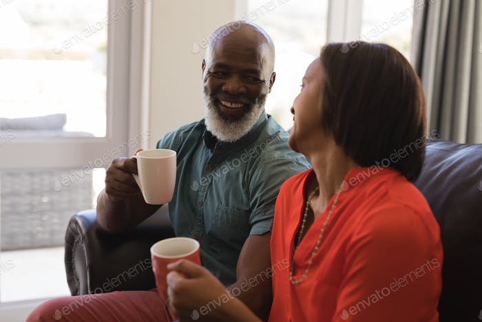 Side view of active senior couple having coffee in living room at home