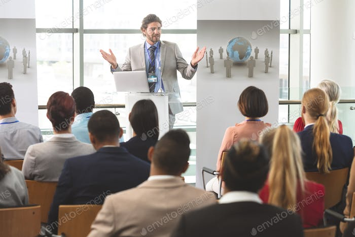 Businessman speaks in front of business colleagues at business seminar in office building
