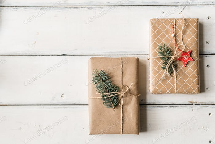 Christmas background with two packed and wrapped giftboxes with conifer on top