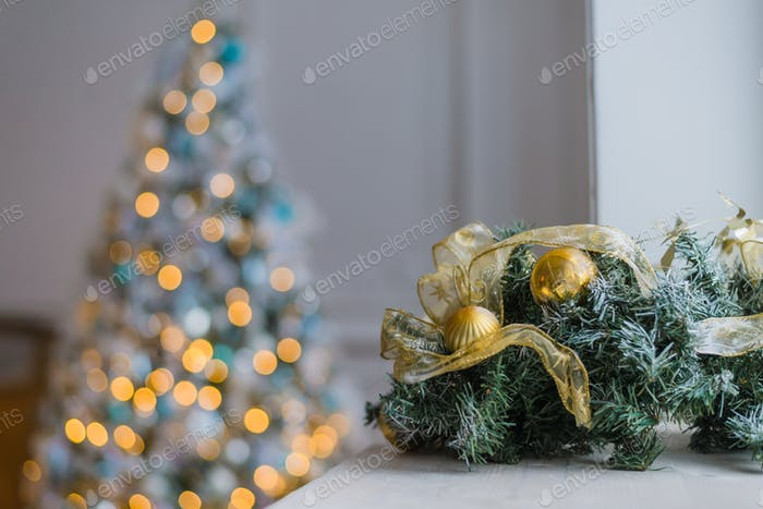 Gold and blue Christmas background of de-focused lights with decorated tree