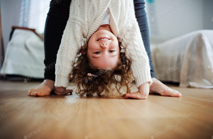 An unrecognizable mother holding small girl upside down at home.