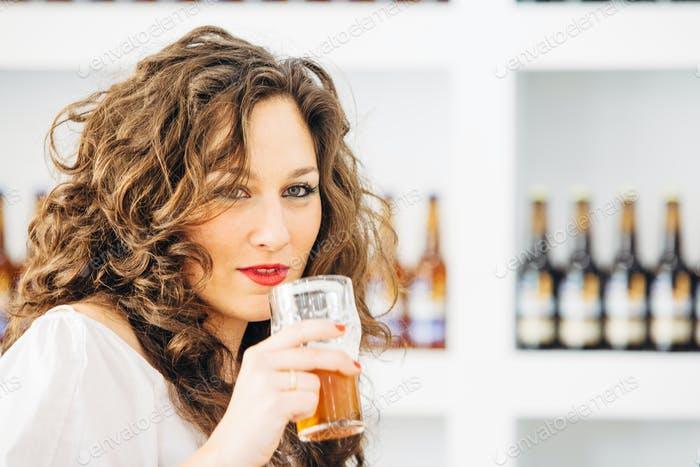 Beautiful woman holding glass of beer