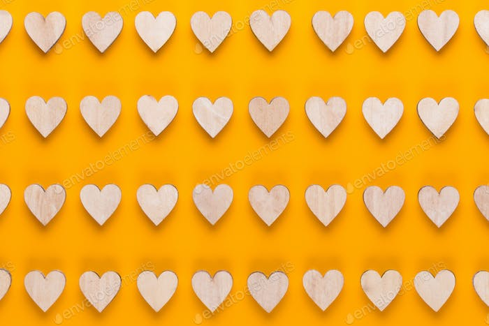 Small wooden hearts on a yellow background.