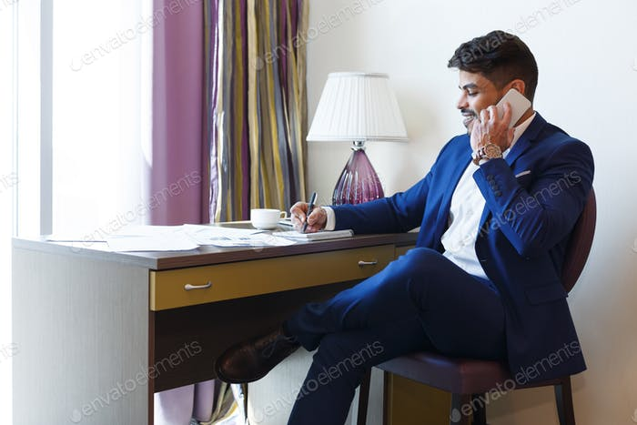 Eastern man in suit working in hotel, talking by phone