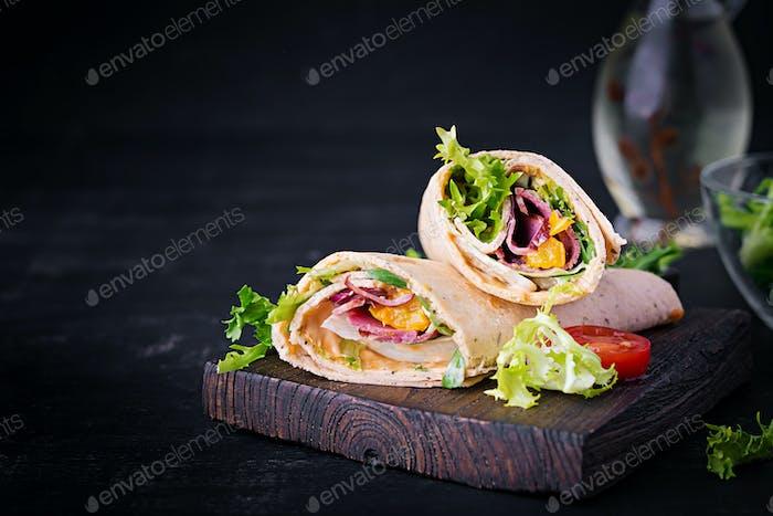 Frische Tortilla-Wraps mit Schinken Rindfleisch und frischem Gemüse auf Holzbrett.