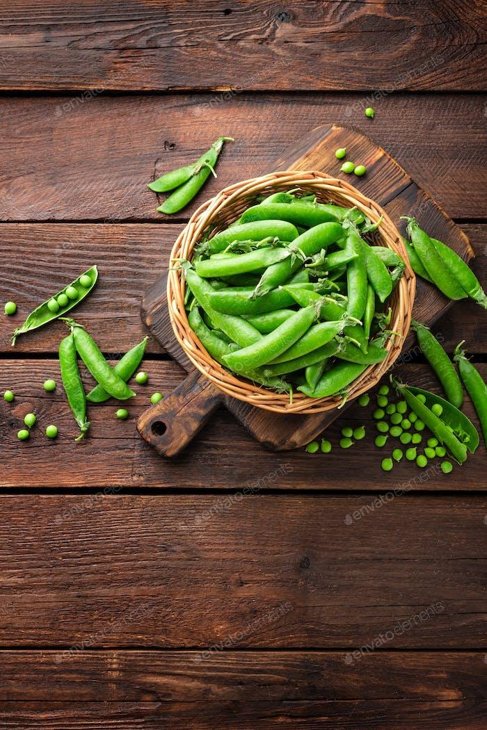 Grüne Erbsen in Schoten und geschält in Holzschale auf dem Tisch
