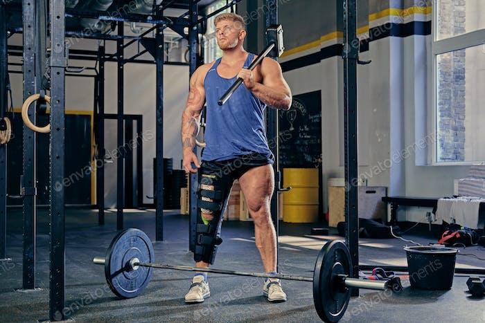 Bodybuilder holds cross fit hammer.
