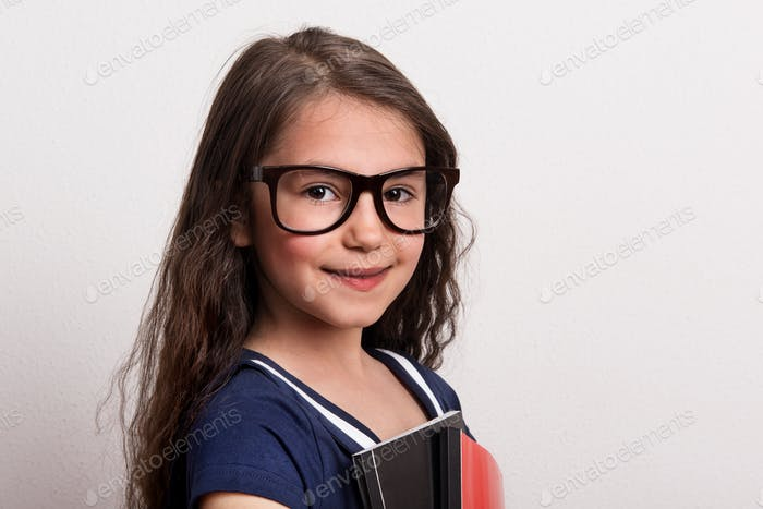 A small schoolgirl with glasses and uniform standing in a studio, holding notepad.